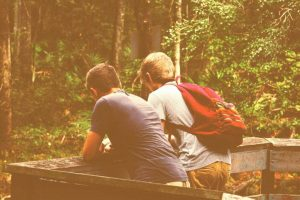 Two friends, side by side, facing a forest. Mental health support.