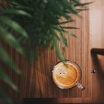 half-filled coffee in clear glass mug beside plant on brown table photo