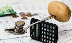 A spoonful of coins with a potato pierced into the other end, balancing on a calculator, depicting a precarious balance of budget.