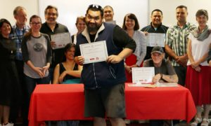 A group of Peer Support workers at their training graduation ceremony; one of the graduates is in the foreground, holding up his certificate proudly.