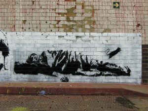 Graffiti art of a homeless person asleep in a sleeping bag