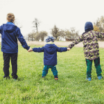 Three children holding hands in a field, with their arms wide open. Photo by Markus Spiske on Unsplash