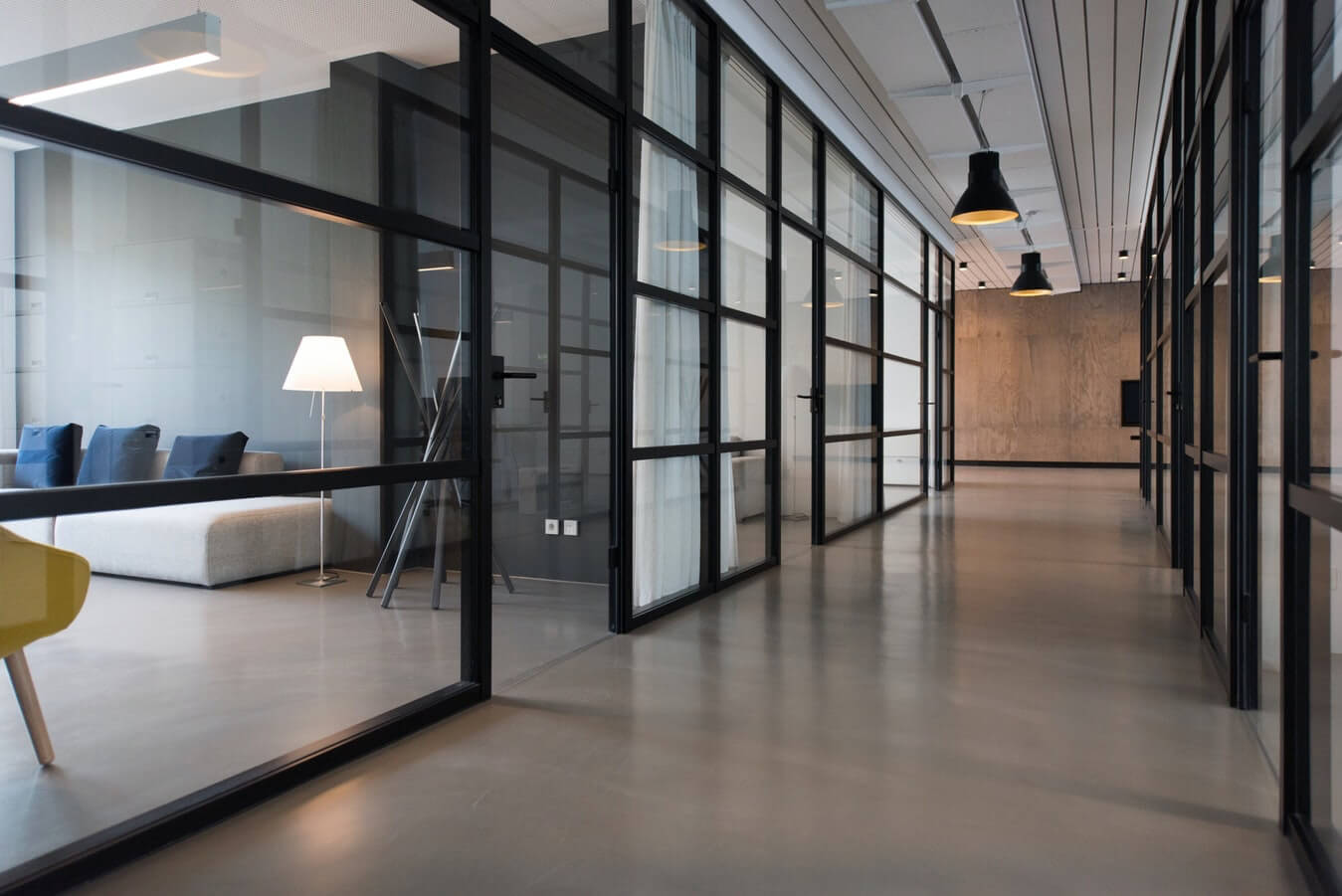 A hallway inside of an office with glass walls on either side