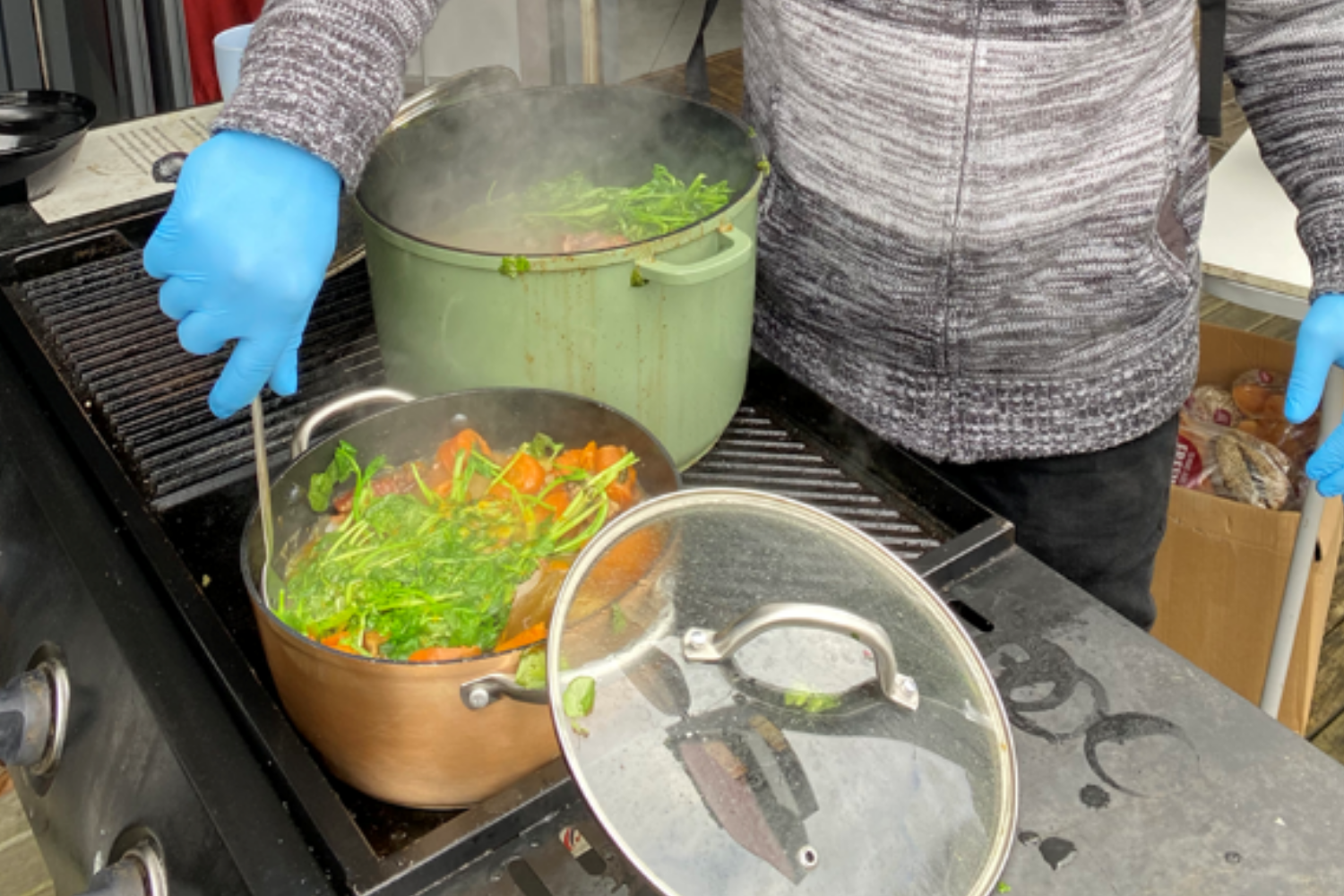 Close-up of a boiling pot of food, man wearing blue gloves stirring the vegetables and boil-up ingredients.
