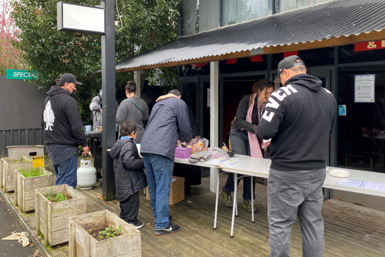 A group of people setting up food on trestle tables outside a motel.